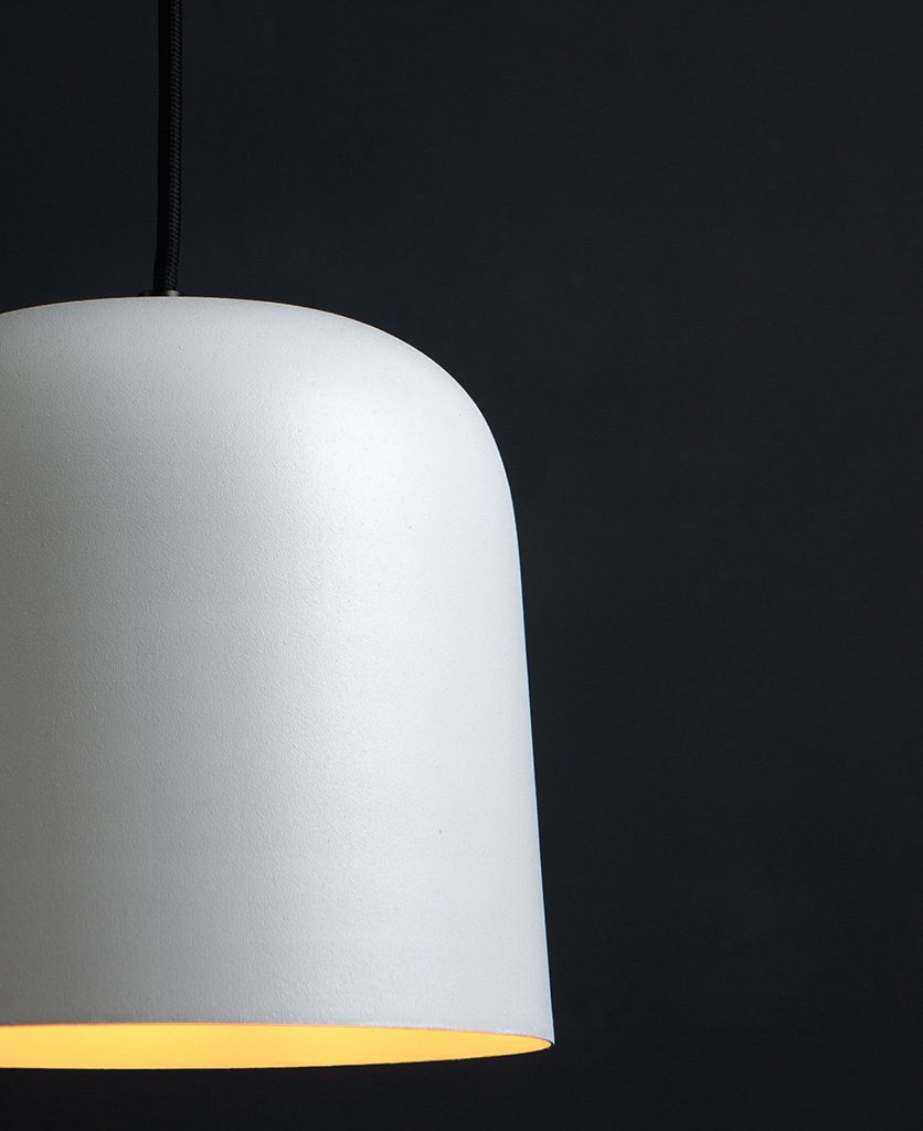 closeup of visby white kitchen pendant lights suspended from black fabric cable against black background