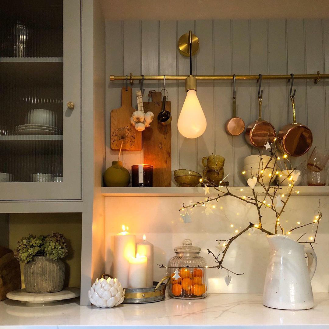 Ritz wall light on a wooden cladded kitchen wall besides copper pans and chopping boards