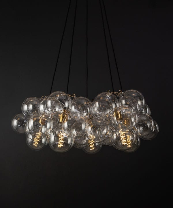 bubble glass chandelier with 40 glass baubles & 5 gold bulb holders suspended from black fabric cable against a black wall