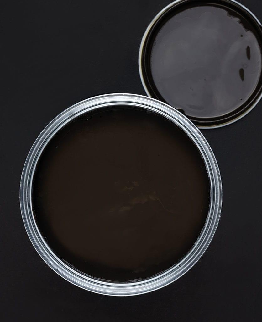 Mud wrestling dark brown paint tin on dark background