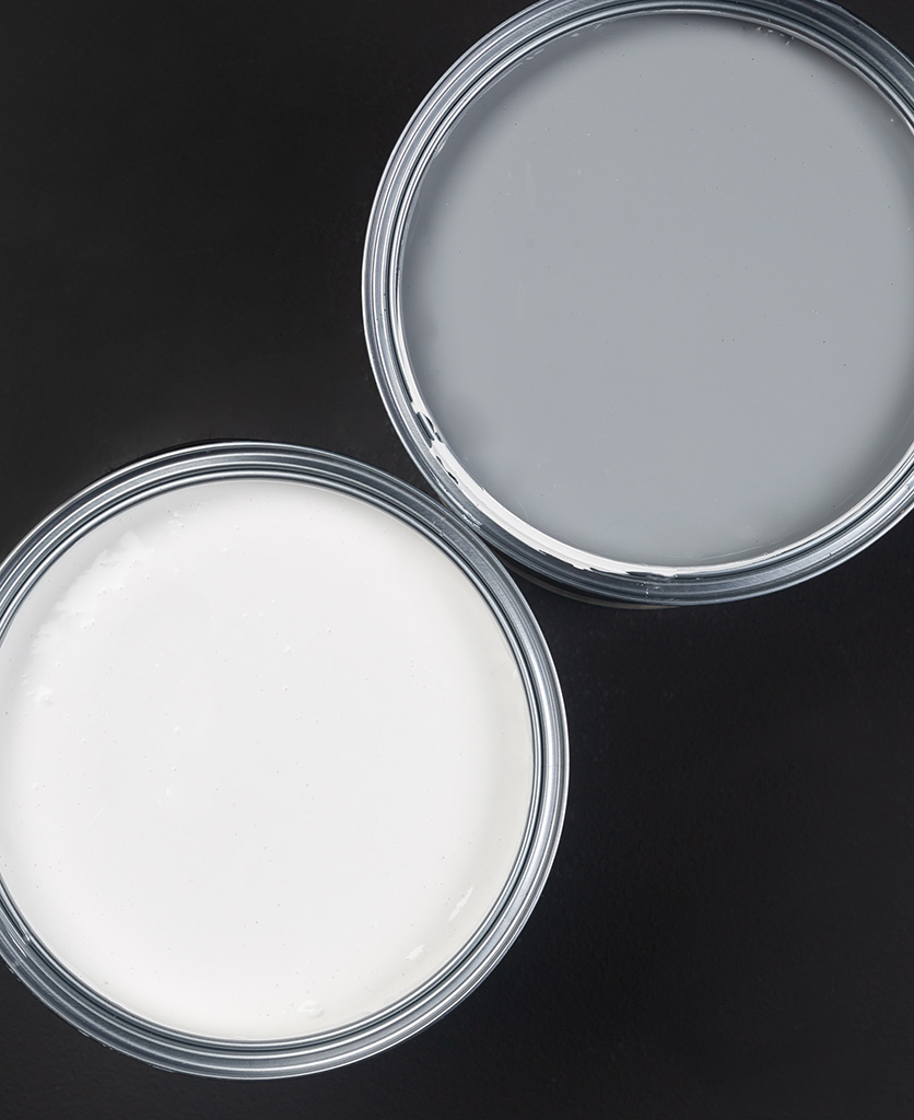 Grey and white paint primer tins on black background