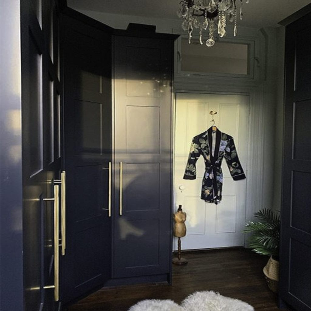 brass skyscraper handles on dark blue cupboards in a blue and white bedroom