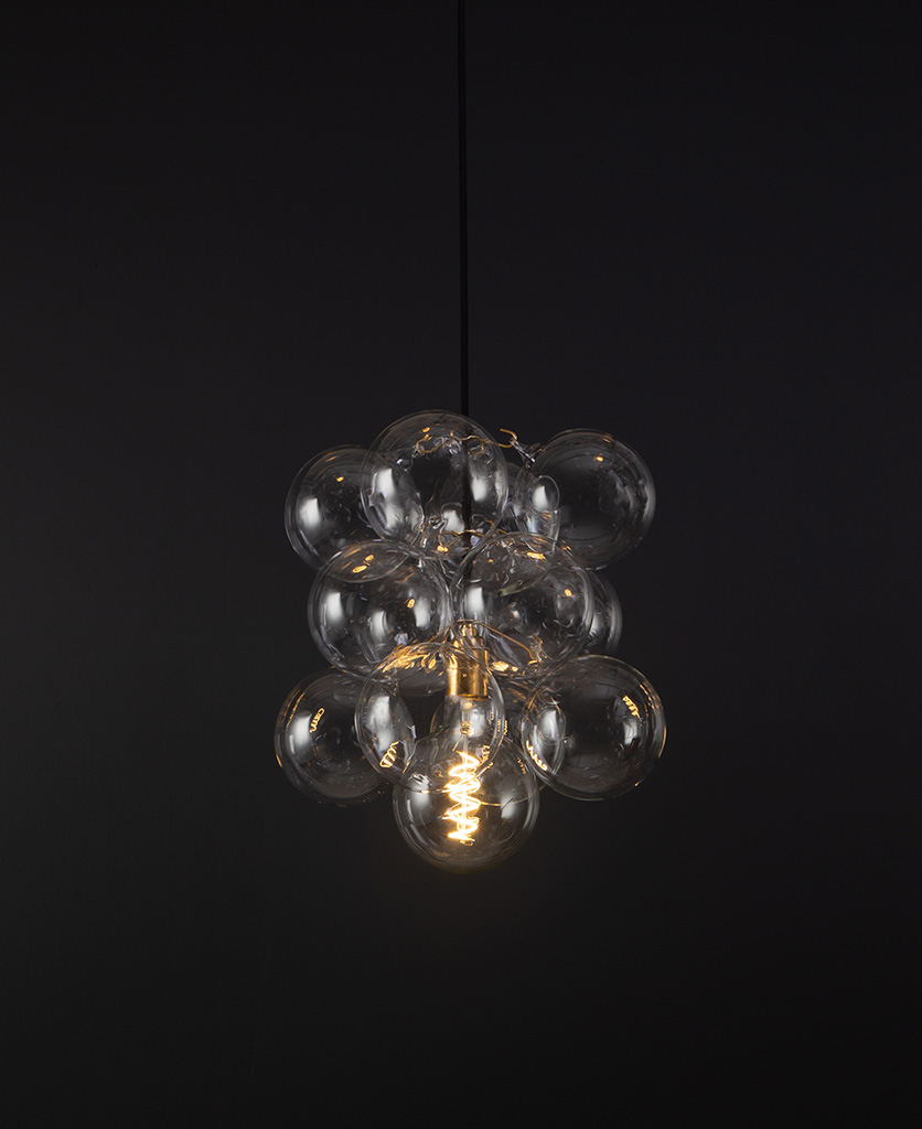 glass bubble light chandelier with 12 clear glass baubles and 1 gold bulb holder suspended from black fabric cable against a black wall