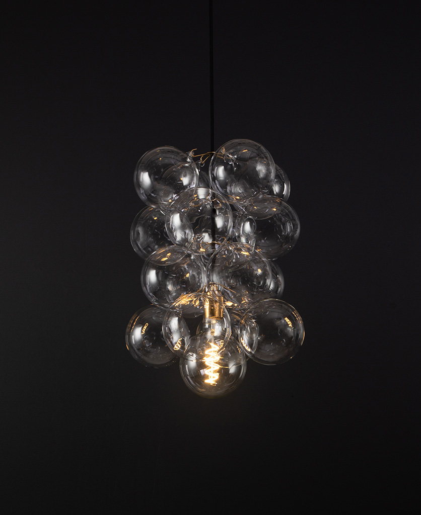 glass bubble light chandelier with 16 clear glass baubles and 1 gold bulb holder suspended from black fabric cable against a black wall