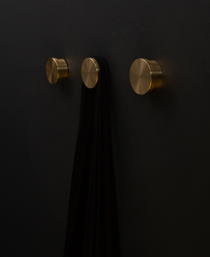 group of three gold baroque metal coat hooks on a black wall