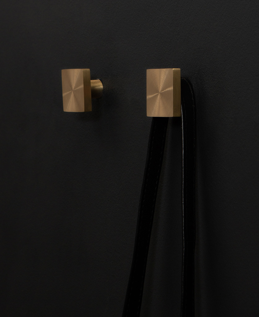 group of two expressionist wall coat hooks in brass on a black wall