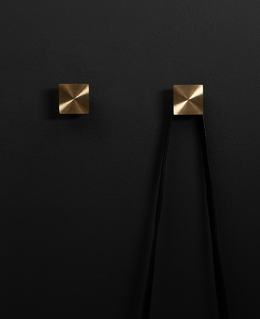 group of two expressionist wall coat hooks in brass on a black wall straight on shot