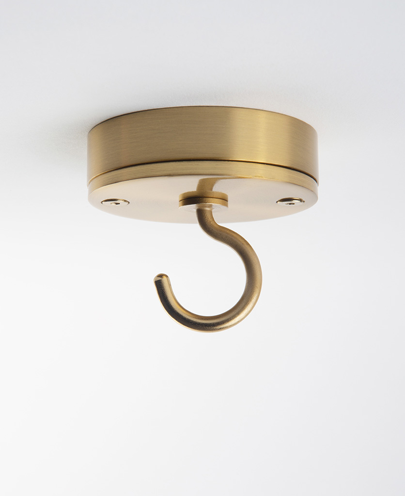 raw brass ceiling hook against white background