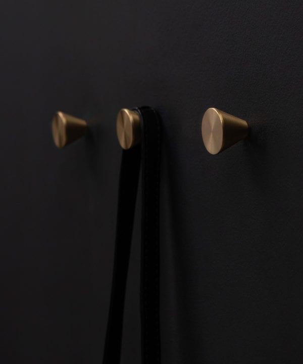 three futurist brass coat hooks on a black wall