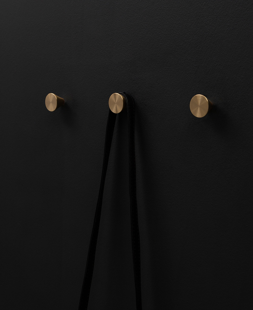 three futurist brass coat hooks on a black wall straight on shot