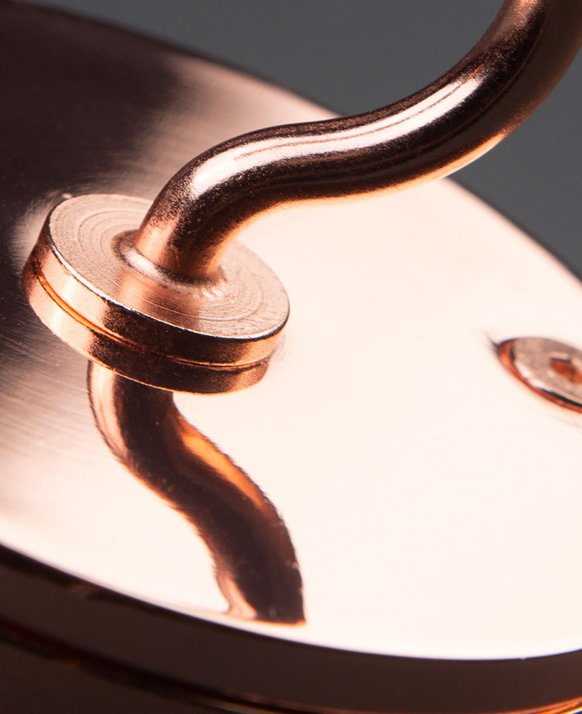 closeup of polished copper ceiling hook against black background