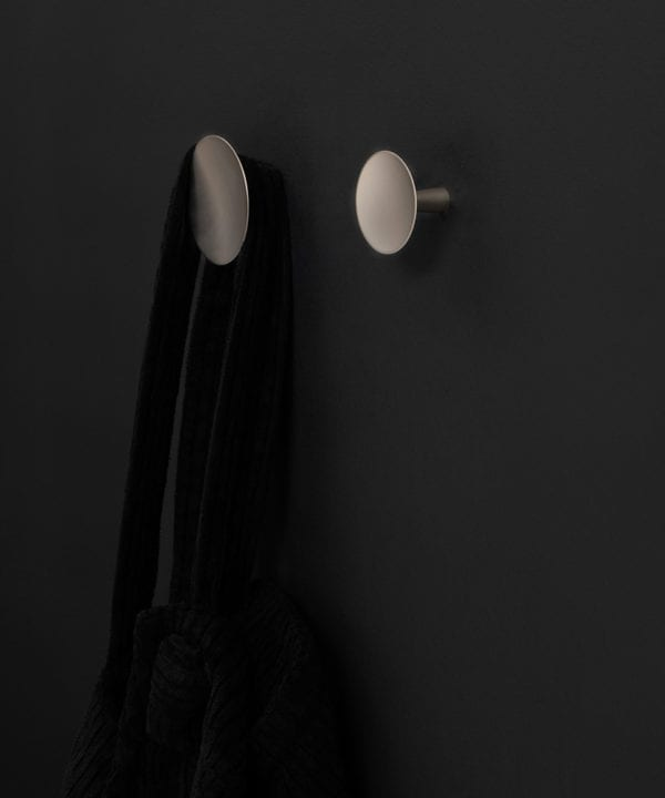two silver Rococo kitchen hooks on a black wall
