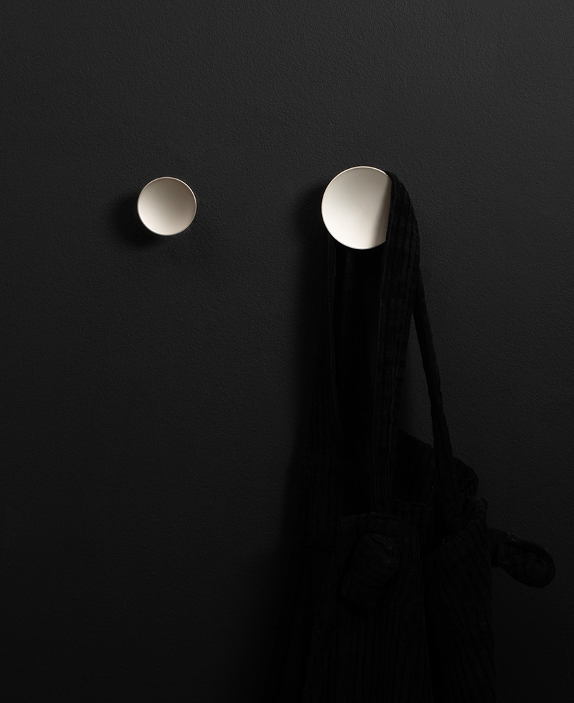 two silver Rococo kitchen hooks on a black wall shot straight on