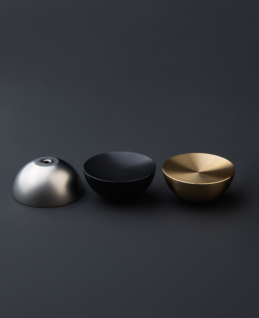 surrealist silver gold and black bowl shaped coat hook against dark grey background