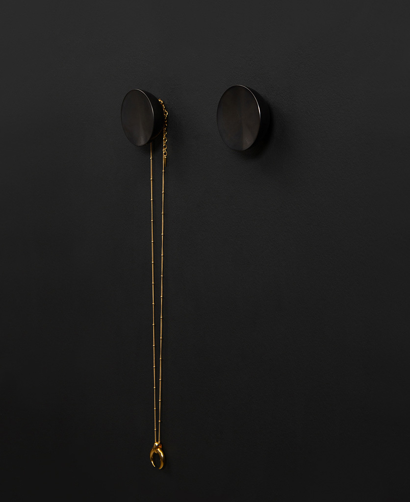 Surrealist coat hook attache to a black wall holding a gold necklace