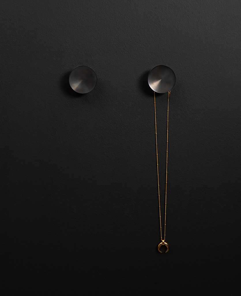 Surrealist coat hook attached to a black wall holding a gold necklace straight on shot