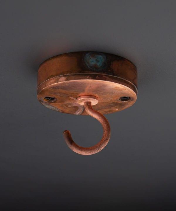 tarnished copper ceiling hook against black background