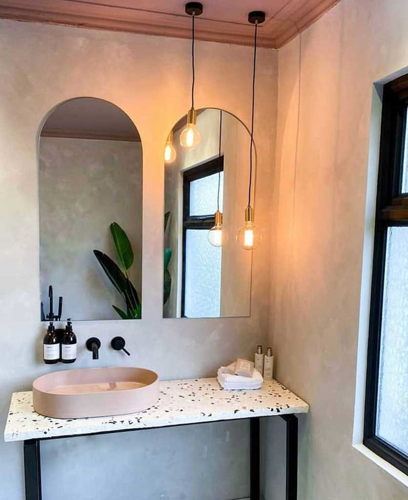 concrete effect bathroom with black tap, soft pink sink and terazzo style table