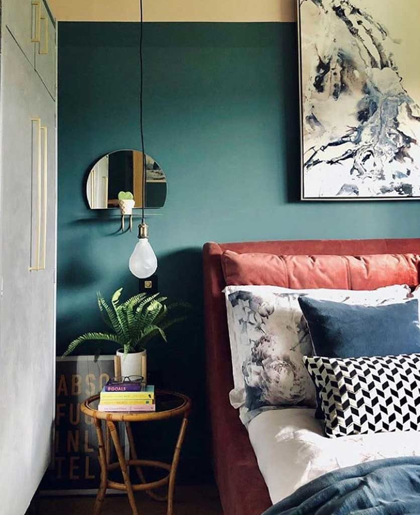 teal and white bedroom with suspended bulb bedside light and coral velvet headboard