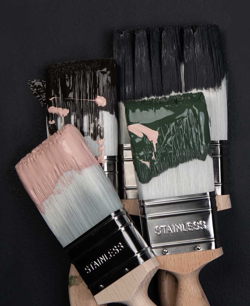 paintbrushes in pink, dark green and black paint against black background