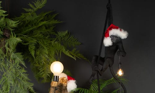 collection of monkey lamps wearing santa hats against a black background