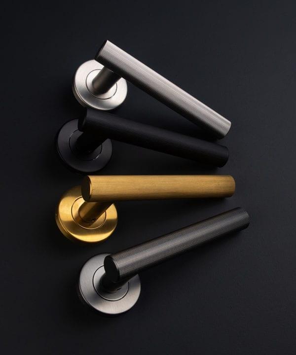group shot of kramer door handles internal in black, graphite, gold and silver on black background