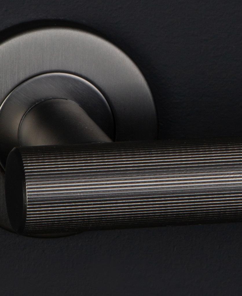 closeup modern door handle graphite on black wall