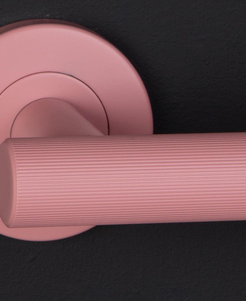 closeup kramer colour pop door handle in pink on black background