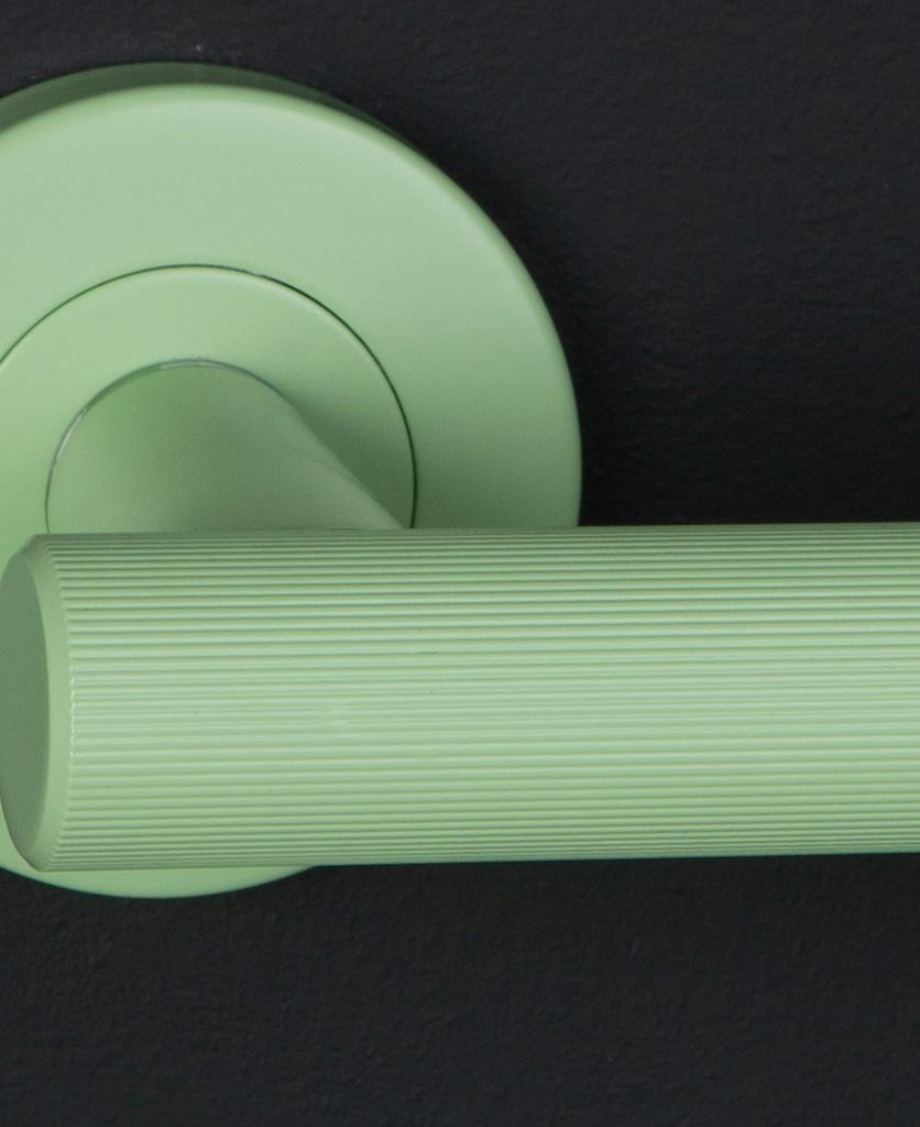 closeup kramer colour pop door handle in green on black background