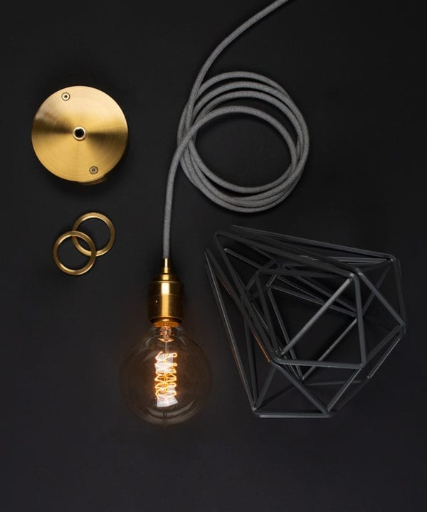 bespoke light fittings gold ceiling rose with grey cage light shade, grey fabric cable, bulb holder and lit bulb on black background