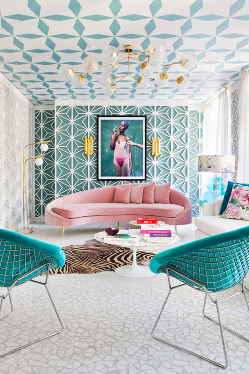 Art Deco style interior with eleborately patterned ceiling, gold lighting and plush pink velvet sofa