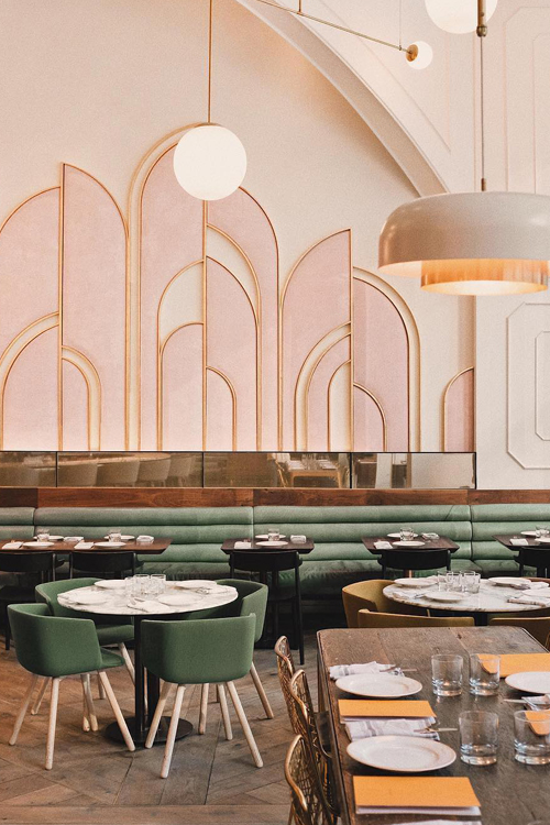 Art Deco style restaurant with sage green banquet seating and sweeping gold and pink arches on the walls