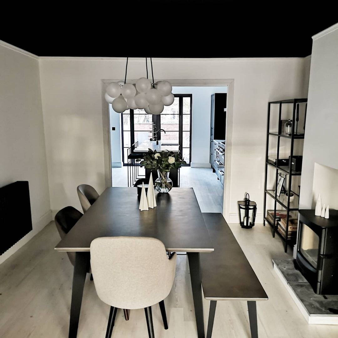 Medium frosted bubble chandelier suspended above dining table in monochrome dining room