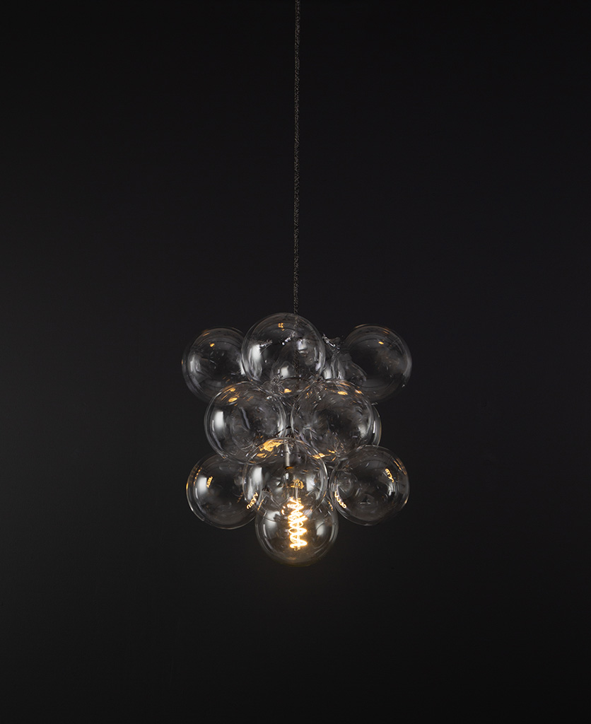 glass bubble light chandelier with 12 clear glass baubles and 1 bronze bulb holder suspended from textured fabric cable against a black wall