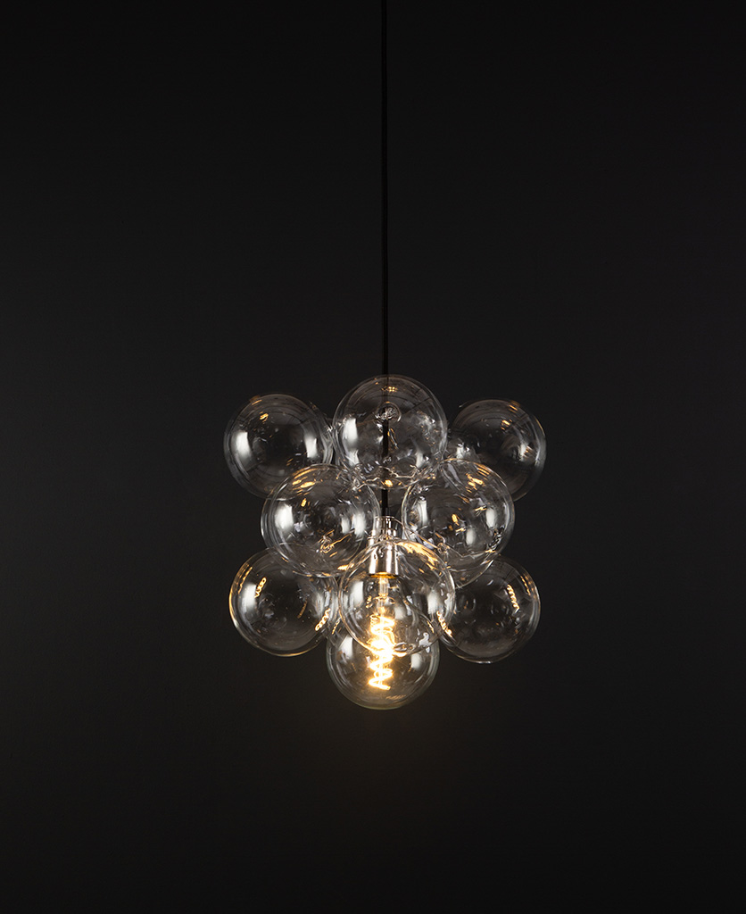 glass bubble light chandelier with 12 clear glass baubles and 1 silver bulb holder suspended from black fabric cable against a black wall