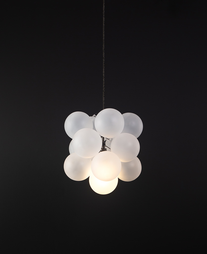 frosted glass bubble chandelier with 12 glass orbs and 1 bronze bulb holder suspended from textured cable against a black wall