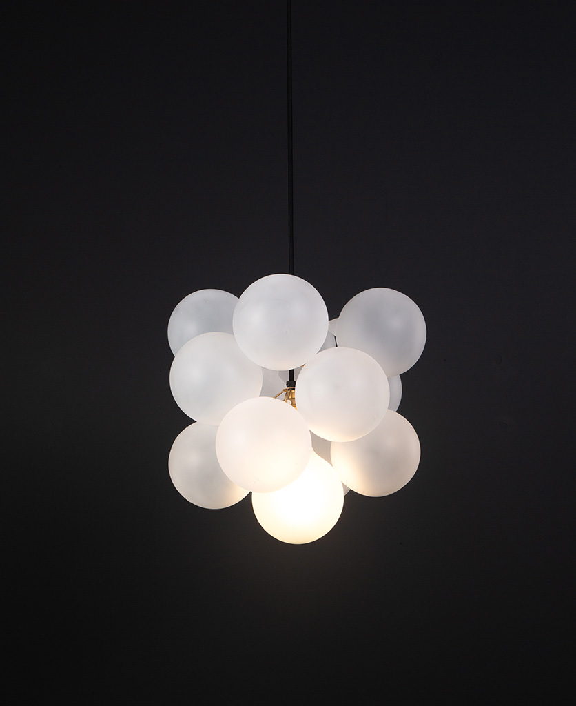 frosted glass bubble chandelier with 12 glass orbs and 1 gold bulb holder suspended from black cable against a black wall