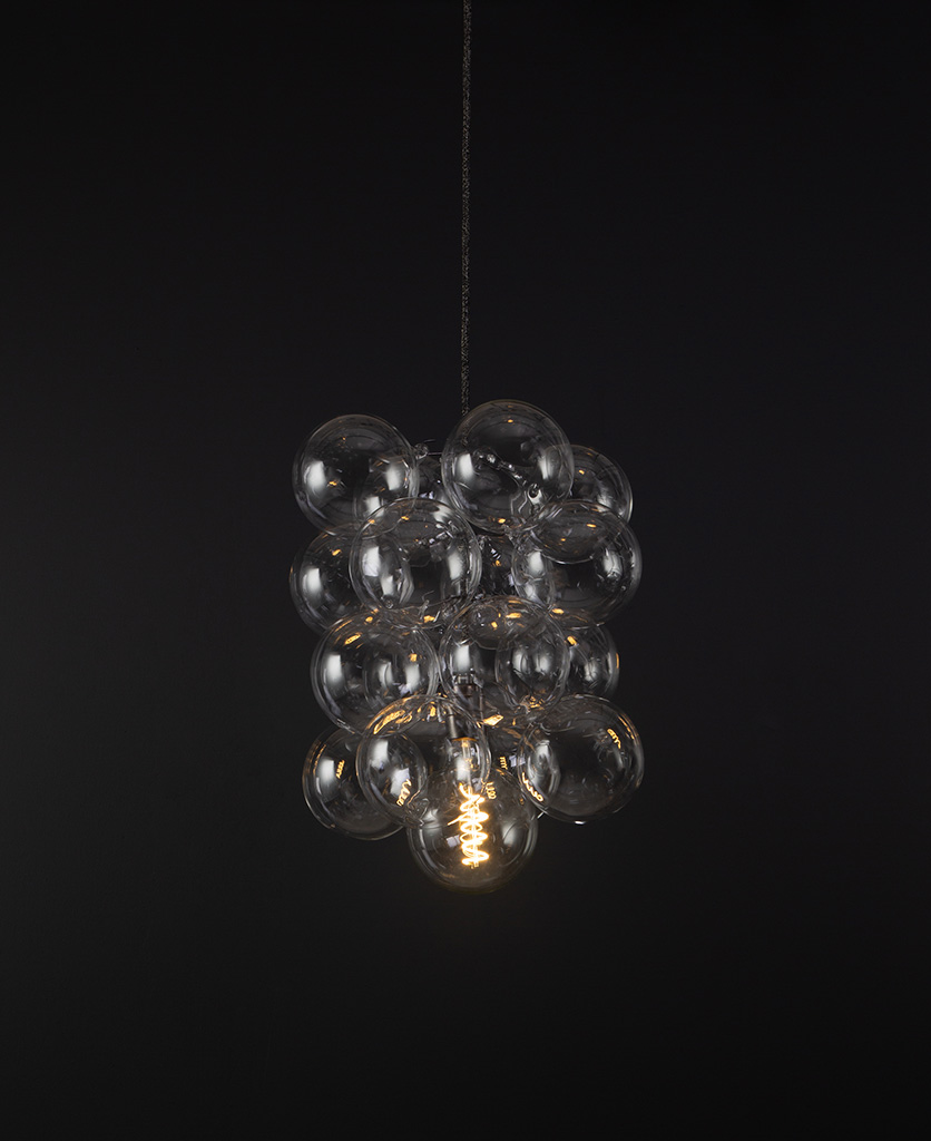 glass bubble light chandelier with 16 clear glass baubles and 1 bronze bulb holder suspended from textured fabric cable against a black wall