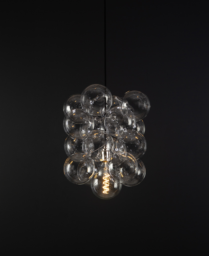 glass bubble light chandelier with 16 clear glass baubles and 1 silver bulb holder suspended from black fabric cable against a black wall