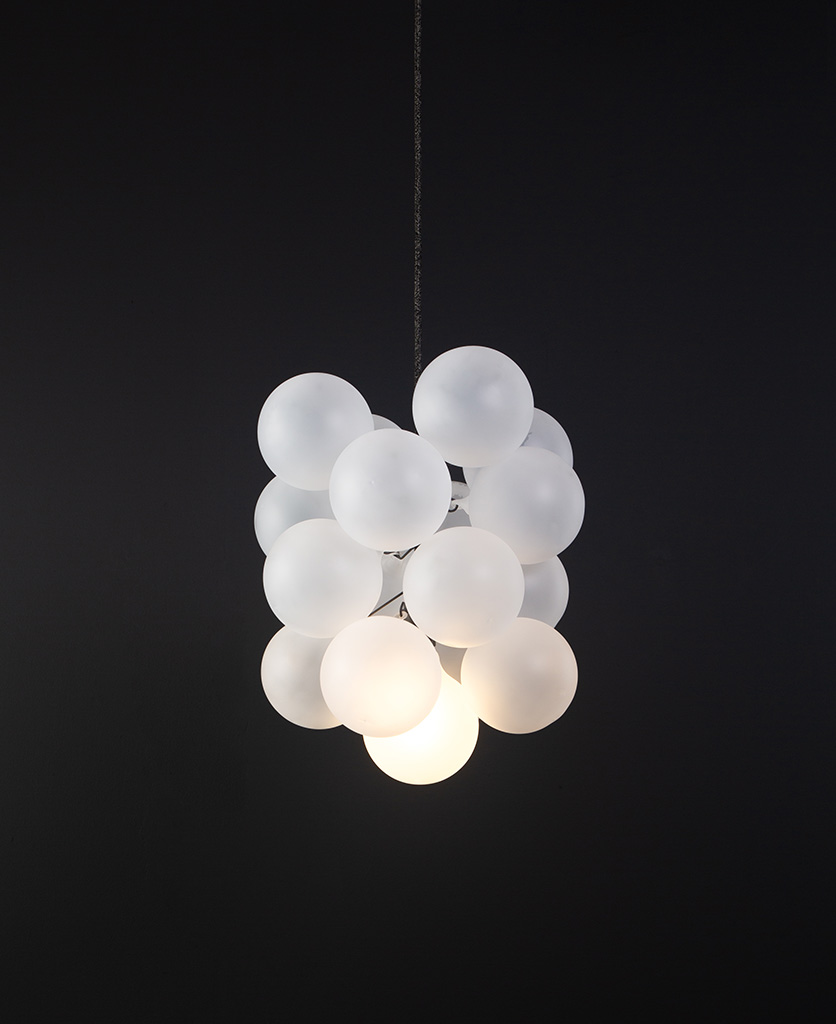 frosted glass bubble chandelier with 16 glass orbs and 1 bronze bulb holder suspended from textured cable against a black wall