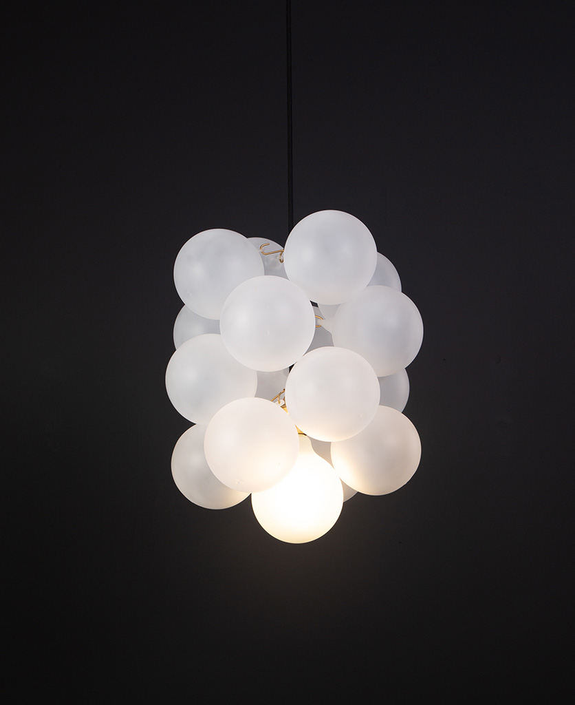 frosted glass bubble chandelier with 16 glass orbs and 1 gold bulb holder suspended from black cable against a black wall