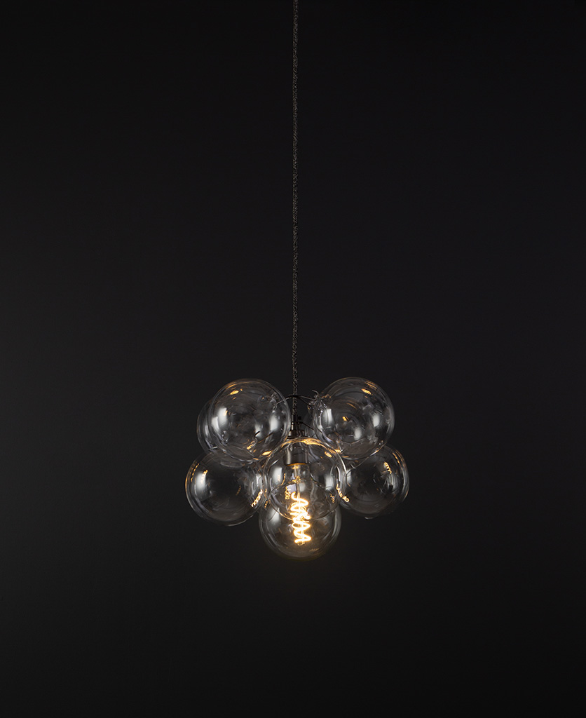 glass bubble light chandelier with 8 clear glass baubles and 1 bronze bulb holder suspended from textured fabric cable against a black wall