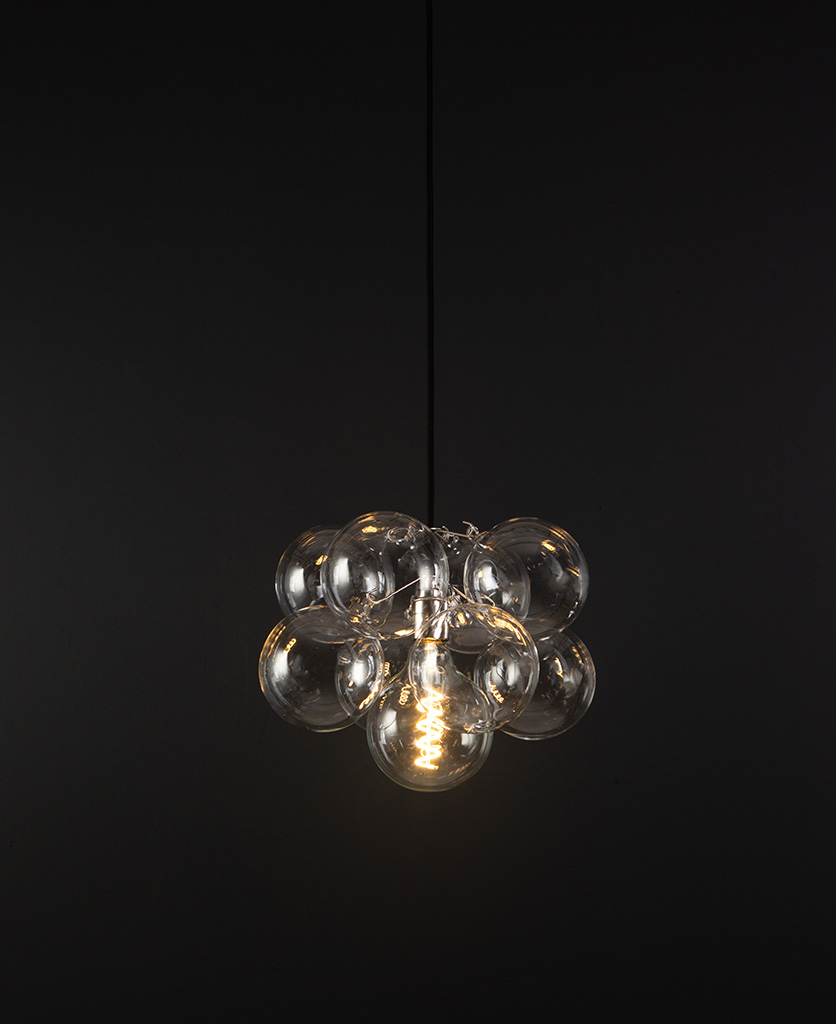 glass bubble light chandelier with 8 clear glass baubles and 1 silver bulb holder suspended from black fabric cable against a black wall