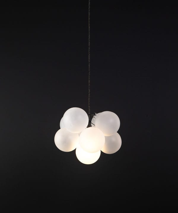 frosted glass bubble chandelier with 8 glass orbs and 1 bronze bulb holder suspended from textured cable against a black wall