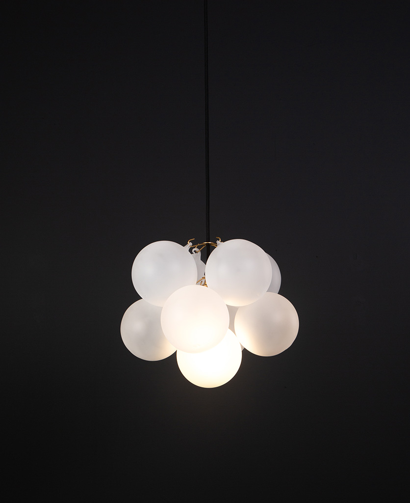 frosted glass bubble chandelier with 8 glass orbs and 1 gold bulb holder suspended from black cable against a black wall