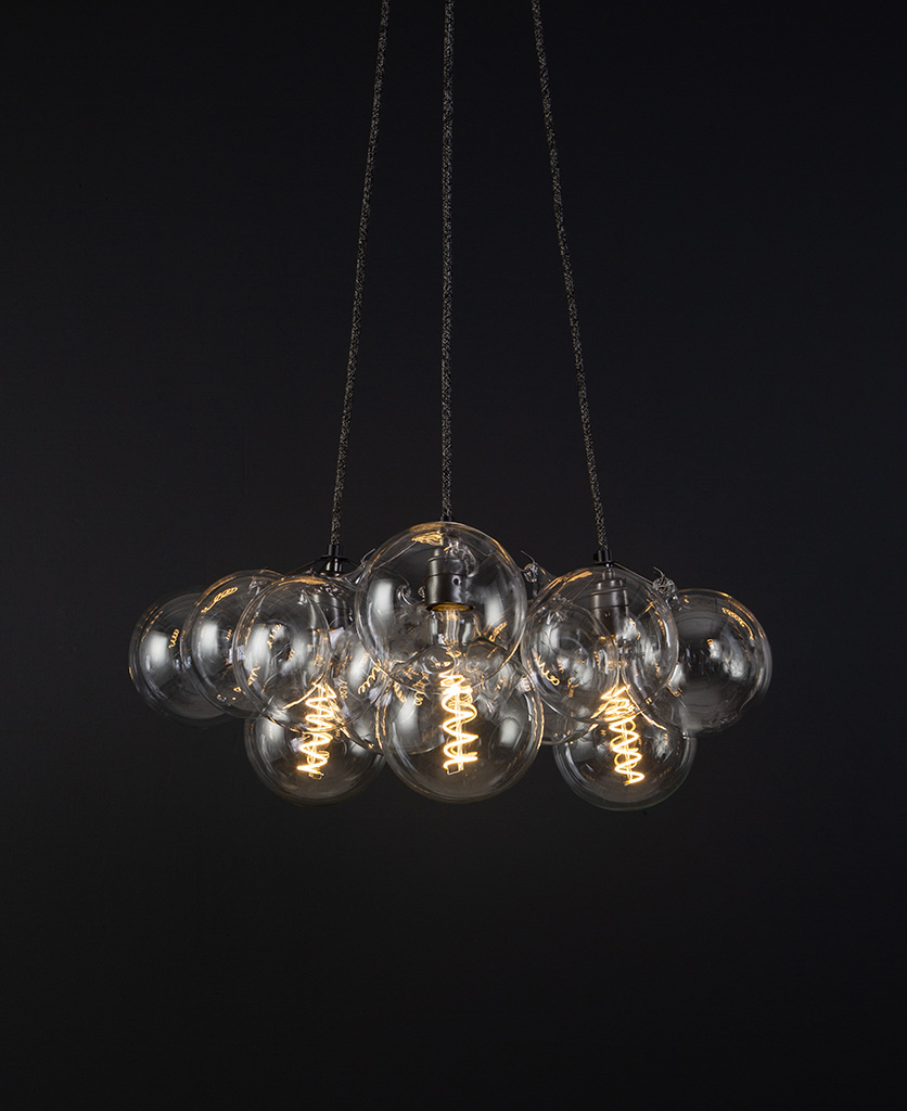 bubble pendant chandelier with 12 clear glass baubles and 3 bronze bulb holders suspended from textured fabric cable against a black wall