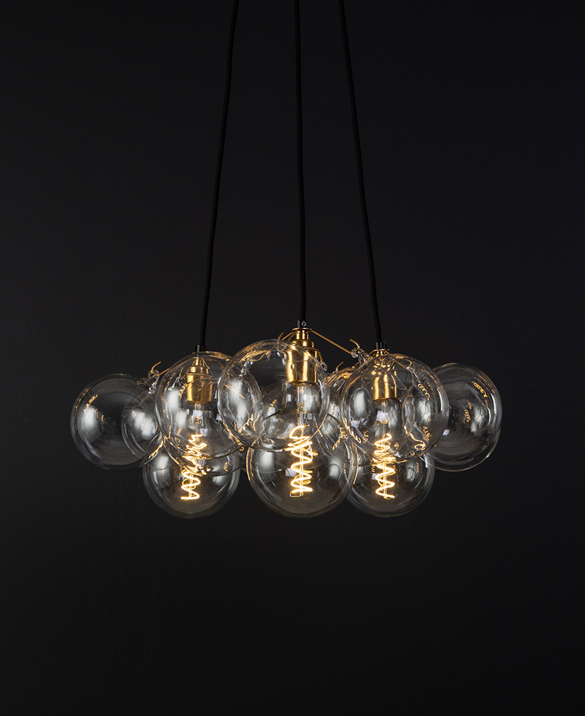 bubble pendant chandelier with 12 clear glass baubles and 3 gold bulb holders suspended from black fabric cable against a black wall