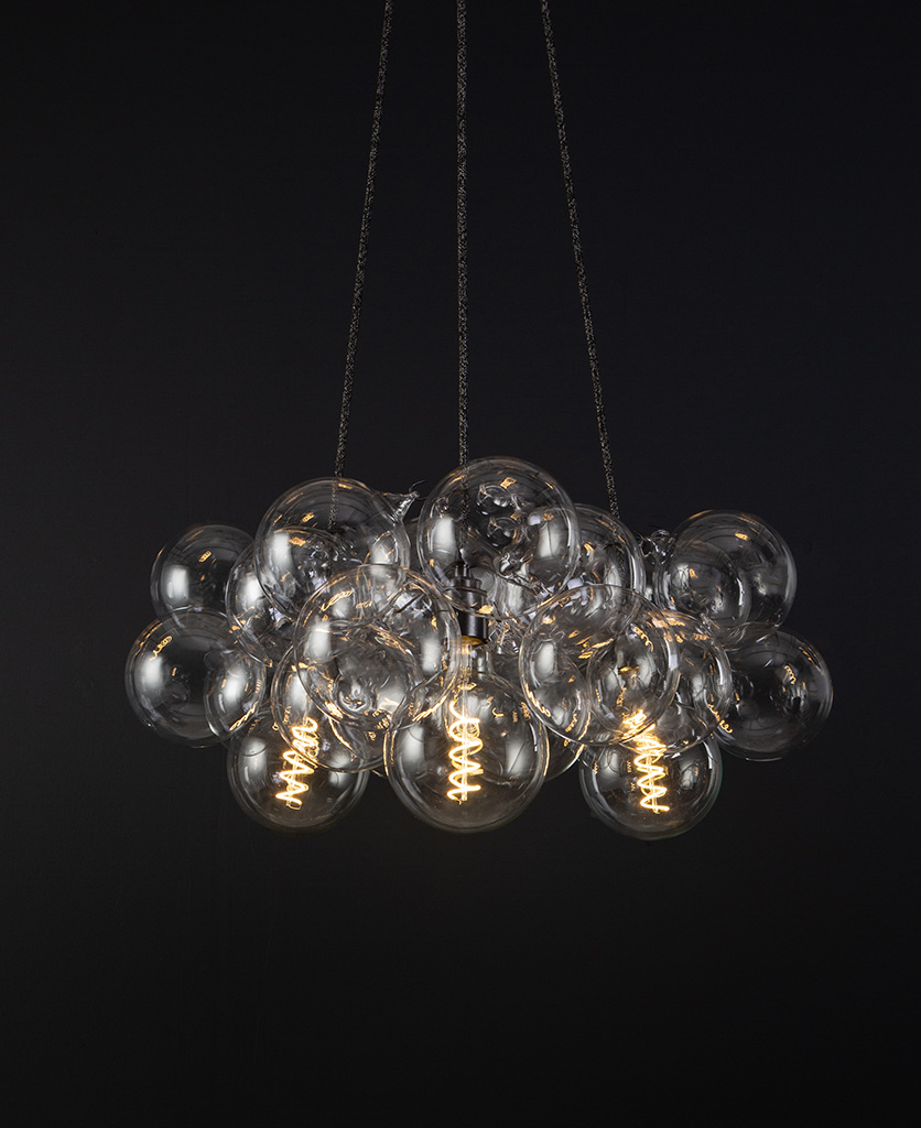 bubble pendant chandelier with 24 clear glass baubles and 3 bronze bulb holders suspended from textured fabric cable against a black wall
