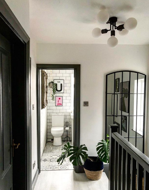 connaught black ceiling light with frosted light bulbs in a black and white hallway