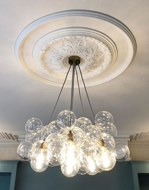 clear bubble chandelier suspended in a blue and white living room